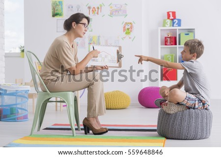 Young woman holding a picture conducting child's psychological test #559648846