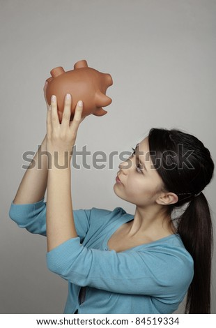 young woman holding a piggy bank hoping she has some money inside