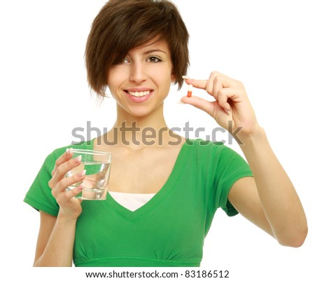 Young woman holding a pill and water, isolated on white