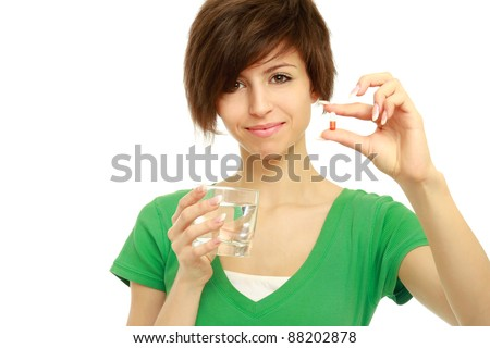 Young woman holding a pill and water, isolated on white background