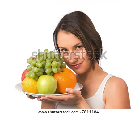 Young woman holding a plate with fresh fruit