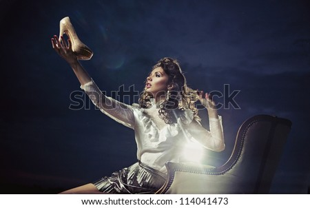 Young woman holding a shoe