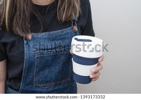 Young woman holding a silicone collapsible cup, reusable coffee tumbler. #1393173332