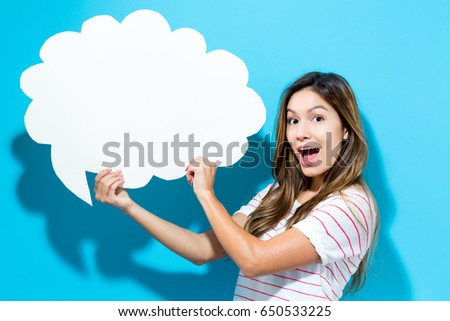 Young woman holding a speech bubble on a blue background