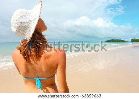 Young woman holding a straw hat and looking to a blue sky