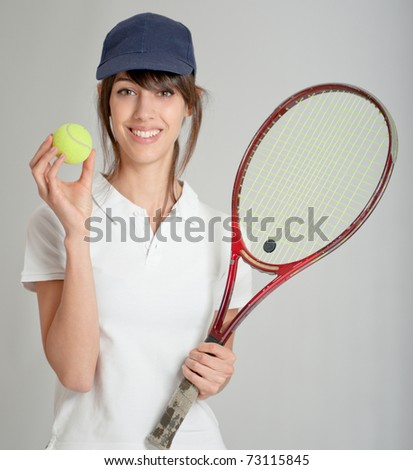 Young woman holding a tennis racket and ball