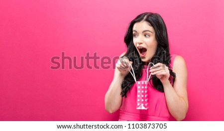 Young woman holding a tiny shopping bag on a pink background #1103873705