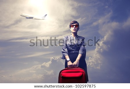 Young woman holding a trolley case with airplane in the background