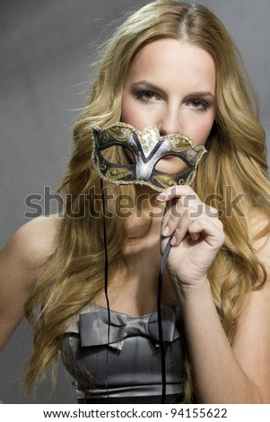 Young woman holding a venetian mask at valentine's day