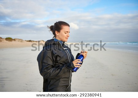 Young woman holding a water bottle while on a walk on the beach in winter