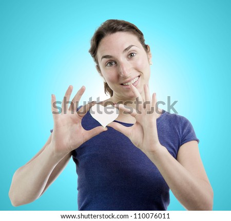 Young woman holding a white heart with both hands over light blue gradient background