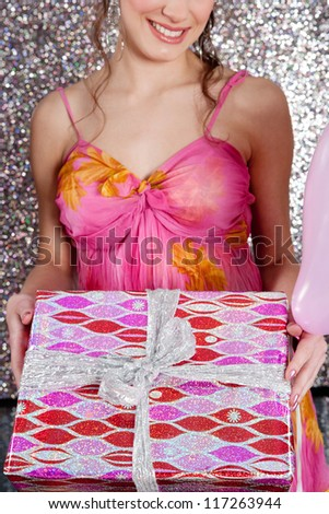 Young woman holding a wrapped gift and a pink balloon against a silver glitter background at a birthday party, smiling.