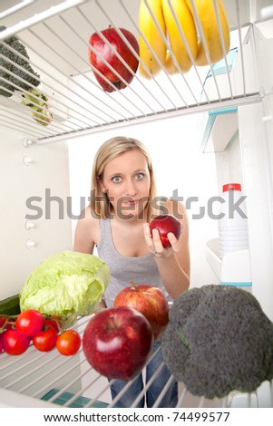 Young woman holding an apple and looking into a refrigerator filled with fruits and vegetables.
