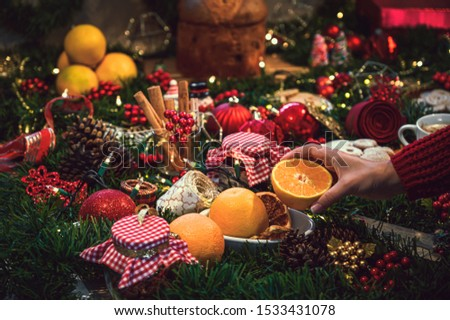 Young woman holding an orange in her hands and in the background a table of Christmas ingredients with ingredients seasonal.