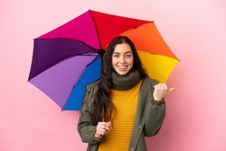 Young woman holding an umbrella isolated on pink background pointing to the side to present a product