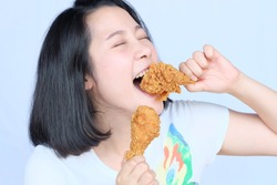 Young woman holding and eating fries chicken