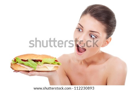 Young woman holding and looking at a sandwich and acting surprised and amased