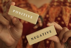 Young woman holding antonym word sign of positive and negative. Two wooden blocks in hands closeup with life option concept.  Choose positive mind or negative thought.