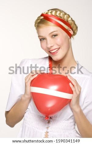 Young woman holding Austrian flag balloon