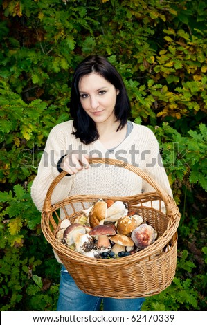 Young woman holding basket with fresh mushrooms