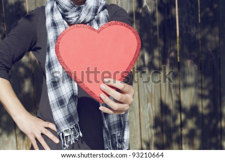 Young woman holding big red heart in her hand, copy space