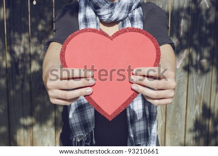 Young woman holding big red heart in her hands, copy space