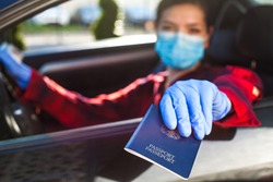 Young woman holding blue passport through car window,patrol border security staff checkpoint control,Coronavirus immunity card health passport,safety and protection from spread and transfer of virus