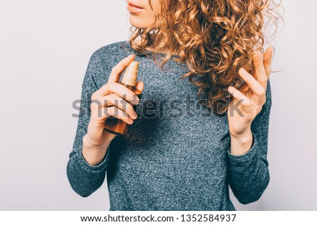Young woman holding bottle with nutritional oil applying on her curly brown hair. Female's hands using cosmetic serum to prevent split ends.
