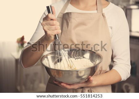 Young woman holding bowl with dough and whisk, closeup #551814253