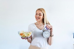 Young woman holding clock and Healthy food of salad Intermittent fasting concept. Time to lose weight , eating control or time to diet concept.