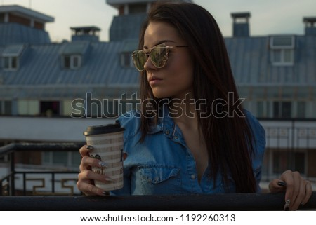 Young woman holding coffee cup on balcony #1192260313