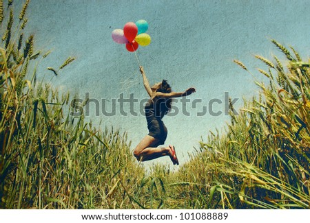 Young woman holding colorful balloons and flying over a meadow.  Photo in old color image style.