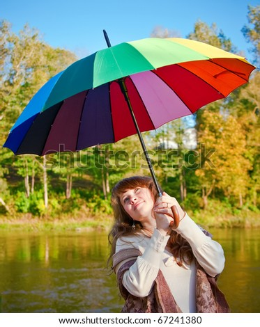 young woman holding colorful umbrella in her arms and looking up
