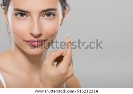 Young woman holding contact lens on index finger with copy space. Close up face of healthy beautiful woman about to wear contact lens. Eyesight and ophthalmology concept.