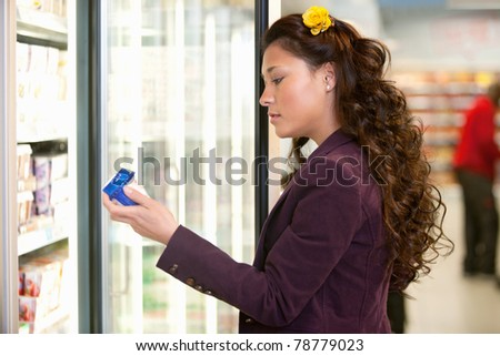 Young woman holding container in front of refrigerator in the supermarket