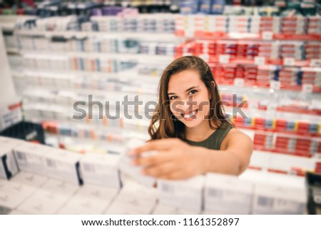 Young woman holding cosmetics in her hand in supermarket. #1161352897