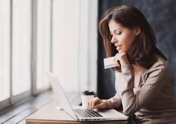 Young woman holding credit card and using laptop computer. Businesswoman working at home. Online shopping, e-commerce, internet banking, spending money, working from home concept
