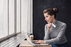Young woman holding credit card and using laptop computer. Girl working online. Online shopping, e-commerce, internet banking, spending money, working from home concept