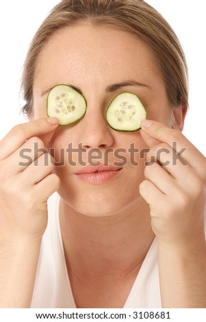 Young woman holding cucumber in front of her eyes