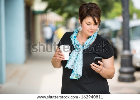 Young woman holding disposable coffee cup while text messaging through smartphone outdoors