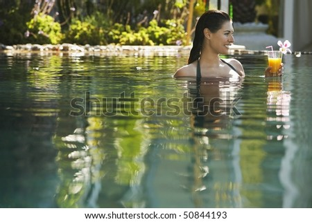 Young woman holding drink in natural swimming pool, portrait
