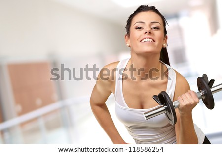 Young woman holding dumbells, indoor