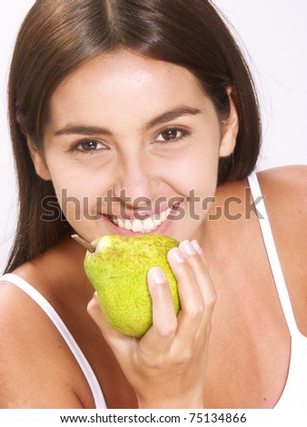 Young woman holding fresh pears. Young woman eating pear.