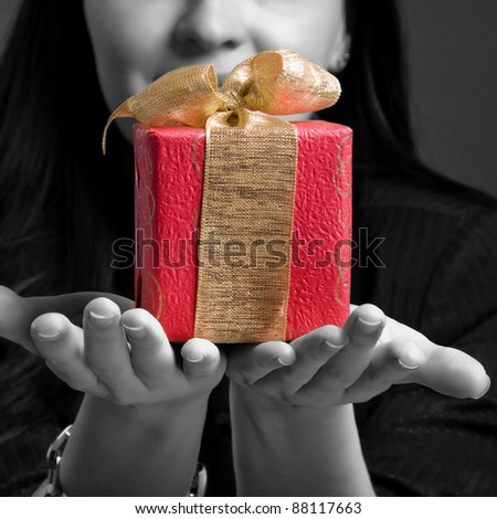 Young woman holding gift against dark background. Black-white image