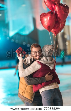 young woman holding gift box and hugging happy boyfriend with heart shaped balloons on rink  #770866294