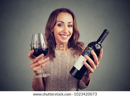 Young woman holding glass of wine and bottle looking happily at camera enjoying taste.