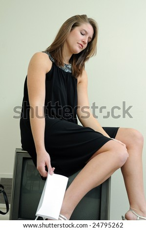 Young woman holding good bye note sitting on TV
