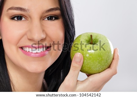 Young woman holding green apple and smiling