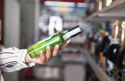 Young woman holding green bottle of alcohol at supermarket.