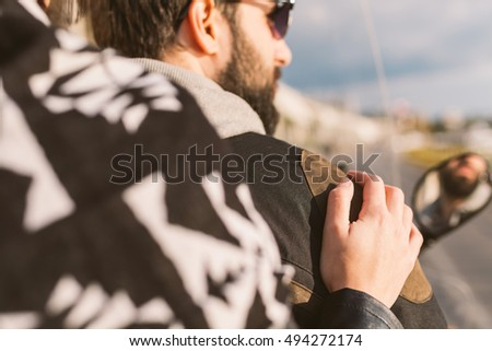 Young woman holding hand on a man's shoulder while riding motorcycle #494272174